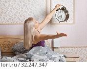 Купить «Счастливая женщина в спальной комнате с большим будильником в руке. Радость от пробуждения.», фото № 32247347, снято 2 октября 2019 г. (c) Элина Гаревская / Фотобанк Лори