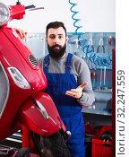 Male worker shows a motorcycle. Стоковое фото, фотограф Яков Филимонов / Фотобанк Лори