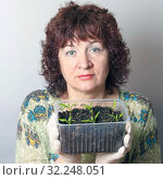 Купить «A female gardener shows a pot with sprouts after a pick.», фото № 32248051, снято 3 апреля 2016 г. (c) Акиньшин Владимир / Фотобанк Лори
