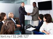 Купить «Two businessman shaking hands in meeting room, confirming successful international partnership», фото № 32248127, снято 12 февраля 2018 г. (c) Яков Филимонов / Фотобанк Лори