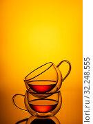 Крепкий черный чай в прозрачных чашках на оранжевом фоне, вертикальный снимок. Стоковое фото, фотограф Sergei Gorin / Фотобанк Лори