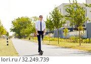 Купить «young businessman riding electric scooter in city», фото № 32249739, снято 1 августа 2019 г. (c) Syda Productions / Фотобанк Лори