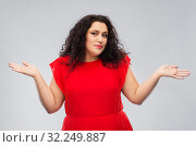 woman in red dress shrugging over grey background. Стоковое фото, фотограф Syda Productions / Фотобанк Лори