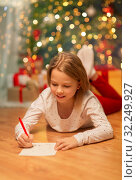 smiling girl writing christmas wish list at home. Стоковое фото, фотограф Syda Productions / Фотобанк Лори