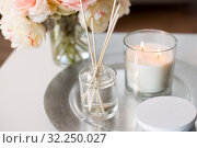 Купить «aroma reed diffuser, candle and flowers on table», фото № 32250027, снято 11 апреля 2019 г. (c) Syda Productions / Фотобанк Лори