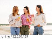 Купить «young women with non alcoholic drinks talking», фото № 32250159, снято 31 августа 2019 г. (c) Syda Productions / Фотобанк Лори