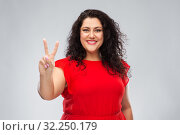 Купить «happy woman in red dress showing peace hand sign», фото № 32250179, снято 15 сентября 2019 г. (c) Syda Productions / Фотобанк Лори