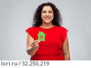 Купить «happy woman in red dress holding green house icon», фото № 32250219, снято 15 сентября 2019 г. (c) Syda Productions / Фотобанк Лори