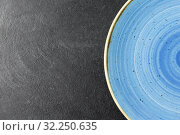 Купить «close up of blue ceramic plate on slate background», фото № 32250635, снято 5 апреля 2018 г. (c) Syda Productions / Фотобанк Лори