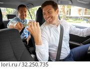 Купить «male car driver taking money from passenger», фото № 32250735, снято 25 августа 2019 г. (c) Syda Productions / Фотобанк Лори