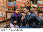 European young man talking to an asian girl holding a smartphone. Стоковое фото, фотограф Евгений Харитонов / Фотобанк Лори