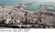 Купить «Aerial view of old town Cadiz with port and buildings at seashore, Spain», видеоролик № 32251507, снято 19 апреля 2019 г. (c) Яков Филимонов / Фотобанк Лори