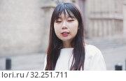 Купить «Portrait of cheerful young chinese longhaired woman talking on a city street», видеоролик № 32251711, снято 20 октября 2019 г. (c) Яков Филимонов / Фотобанк Лори