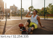 Купить «Basketball player drinks water on outdoor court», фото № 32254335, снято 13 июня 2019 г. (c) Tryapitsyn Sergiy / Фотобанк Лори