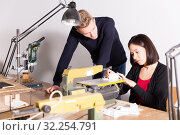 Teacher helping girl making architectural elements on scroll saw. Стоковое фото, фотограф Яков Филимонов / Фотобанк Лори