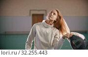 Купить «A young woman fencer with long hair takes off the helmet and smile», видеоролик № 32255443, снято 1 апреля 2020 г. (c) Константин Шишкин / Фотобанк Лори