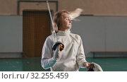 Купить «A young woman fencer with long blonde hair takes off a protective helmet holding a sword», видеоролик № 32255459, снято 10 апреля 2020 г. (c) Константин Шишкин / Фотобанк Лори