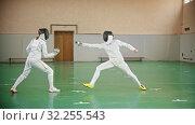 Купить «Two young women at fencing training in the school gym», видеоролик № 32255543, снято 1 апреля 2020 г. (c) Константин Шишкин / Фотобанк Лори