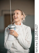 Купить «A young smiling woman fencer standing in the gym with a sword up and looking at it», фото № 32255627, снято 5 октября 2019 г. (c) Константин Шишкин / Фотобанк Лори