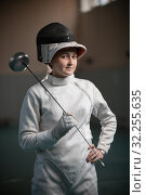 Купить «A young woman fencer with an open helmet on standing in the gym», фото № 32255635, снято 5 октября 2019 г. (c) Константин Шишкин / Фотобанк Лори