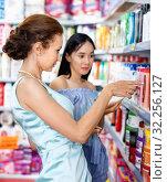 Купить «Stylish female and girl attentively looking haircare products at shop», фото № 32256127, снято 21 июня 2018 г. (c) Яков Филимонов / Фотобанк Лори
