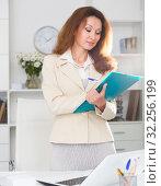 Купить «Female office worker is talking about documents for signing», фото № 32256199, снято 30 мая 2018 г. (c) Яков Филимонов / Фотобанк Лори