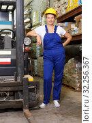 Купить «Woman worker in helmet standing near car in warehouse of modern build store», фото № 32256367, снято 20 сентября 2018 г. (c) Яков Филимонов / Фотобанк Лори