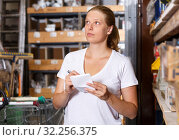 Купить «Female customer holding shop list and looking tools at shelves in build store», фото № 32256375, снято 20 сентября 2018 г. (c) Яков Филимонов / Фотобанк Лори
