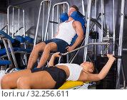 Купить «Young well trained woman lying on back on bench and lifting weights in shoulder press machinery», фото № 32256611, снято 19 октября 2019 г. (c) Яков Филимонов / Фотобанк Лори