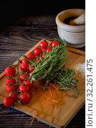 Купить «Fresh tomato cherry, green leaves of rosemary herbs, salt and unprepared spaghetti on wooden board above view, background restaurant decoration», фото № 32261475, снято 14 сентября 2019 г. (c) Alexander Tihonovs / Фотобанк Лори