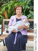 Купить «Loving grandmother sitting with her newborn baby grandson in bench next to a big garden», фото № 32262139, снято 31 августа 2019 г. (c) Кекяляйнен Андрей / Фотобанк Лори