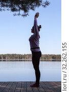 Купить «Woman standing in yoga position on pier of lake at morning», фото № 32262155, снято 1 мая 2016 г. (c) Кекяляйнен Андрей / Фотобанк Лори