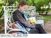 Купить «Adult mother looking at her eating baby, breast feeding on the street, woman sitting on the bench», фото № 32262159, снято 24 августа 2019 г. (c) Кекяляйнен Андрей / Фотобанк Лори
