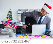 Young businessman celebrating christmas in the office. Стоковое фото, фотограф Elnur / Фотобанк Лори