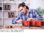 Купить «Young handsome repairman repairing cello», фото № 32262671, снято 4 апреля 2019 г. (c) Elnur / Фотобанк Лори