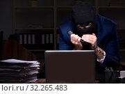 Купить «Male employee stealing information in the office night time», фото № 32265483, снято 22 апреля 2019 г. (c) Elnur / Фотобанк Лори
