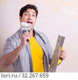 Купить «Young man applying plaster on wall at home», фото № 32267659, снято 15 марта 2018 г. (c) Elnur / Фотобанк Лори
