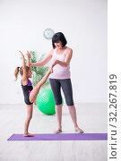 Купить «Girl and mother exercising at home», фото № 32267819, снято 16 июля 2019 г. (c) Elnur / Фотобанк Лори