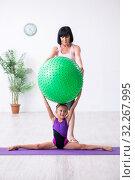 Купить «Girl and mother exercising at home», фото № 32267995, снято 16 июля 2019 г. (c) Elnur / Фотобанк Лори