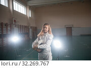 Купить «A portrait of a young woman fencer holding her helmet at the school gym», фото № 32269767, снято 5 октября 2019 г. (c) Константин Шишкин / Фотобанк Лори