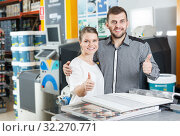 Купить «Young family standing and holding thumb up in tools store», фото № 32270771, снято 17 мая 2018 г. (c) Яков Филимонов / Фотобанк Лори