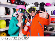 Купить «Happy couple in skiing gear taking selfie during shopping», фото № 32270851, снято 6 февраля 2018 г. (c) Яков Филимонов / Фотобанк Лори