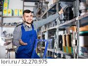 Купить «Male worker deciding on flexible ventilation pipe in workshop», фото № 32270975, снято 15 марта 2017 г. (c) Яков Филимонов / Фотобанк Лори