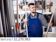 Купить «Production worker in uniform with plastic trim corners», фото № 32270983, снято 15 марта 2017 г. (c) Яков Филимонов / Фотобанк Лори