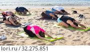 Купить «Sporty people practicing yoga on beach», фото № 32275851, снято 14 июня 2017 г. (c) Яков Филимонов / Фотобанк Лори