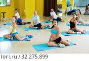 Купить «Group of people practicing yoga in dance hall», фото № 32275899, снято 21 июня 2017 г. (c) Яков Филимонов / Фотобанк Лори