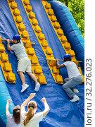 Купить «Males climbing on inflatable slide», фото № 32276023, снято 29 мая 2019 г. (c) Яков Филимонов / Фотобанк Лори