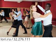 Купить «Positive adult couples dancing tango together in modern studio», фото № 32276111, снято 4 октября 2018 г. (c) Яков Филимонов / Фотобанк Лори