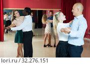 Купить «Positive people learning to dance classical dance together in dancing class», фото № 32276151, снято 4 октября 2018 г. (c) Яков Филимонов / Фотобанк Лори
