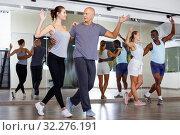 Adult dancing couples enjoying active boogie-woogie in modern studio. Стоковое фото, фотограф Яков Филимонов / Фотобанк Лори